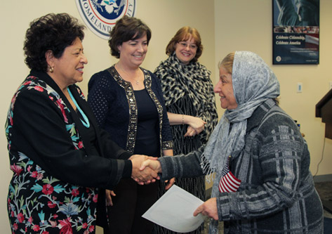 Photo of Director Achuleta, Sarah Taylor (District Director US Citizenship and Immigration Services), Kimbelry Zanotti (Field Office Director US Citizenship and Immigration Services) and a woman who is becoming a citizen.