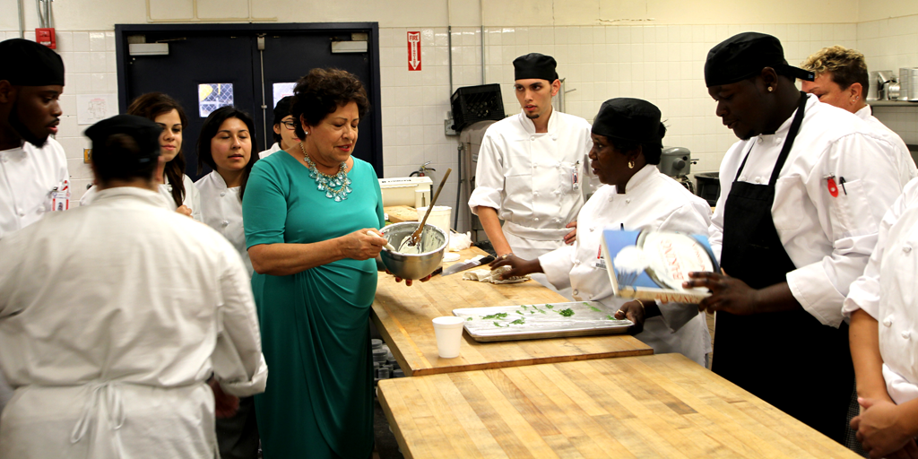 Director Archuleta in a green dress stiring food in a bowl. She is surrounded by several people in chef jackets
