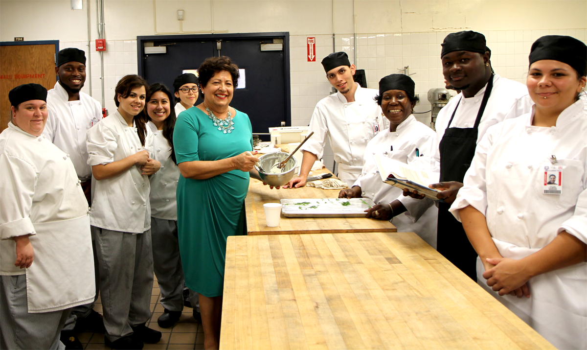 Director Archuleta in green dress surrounded by high school students in cooking jackets. All in kitchen.