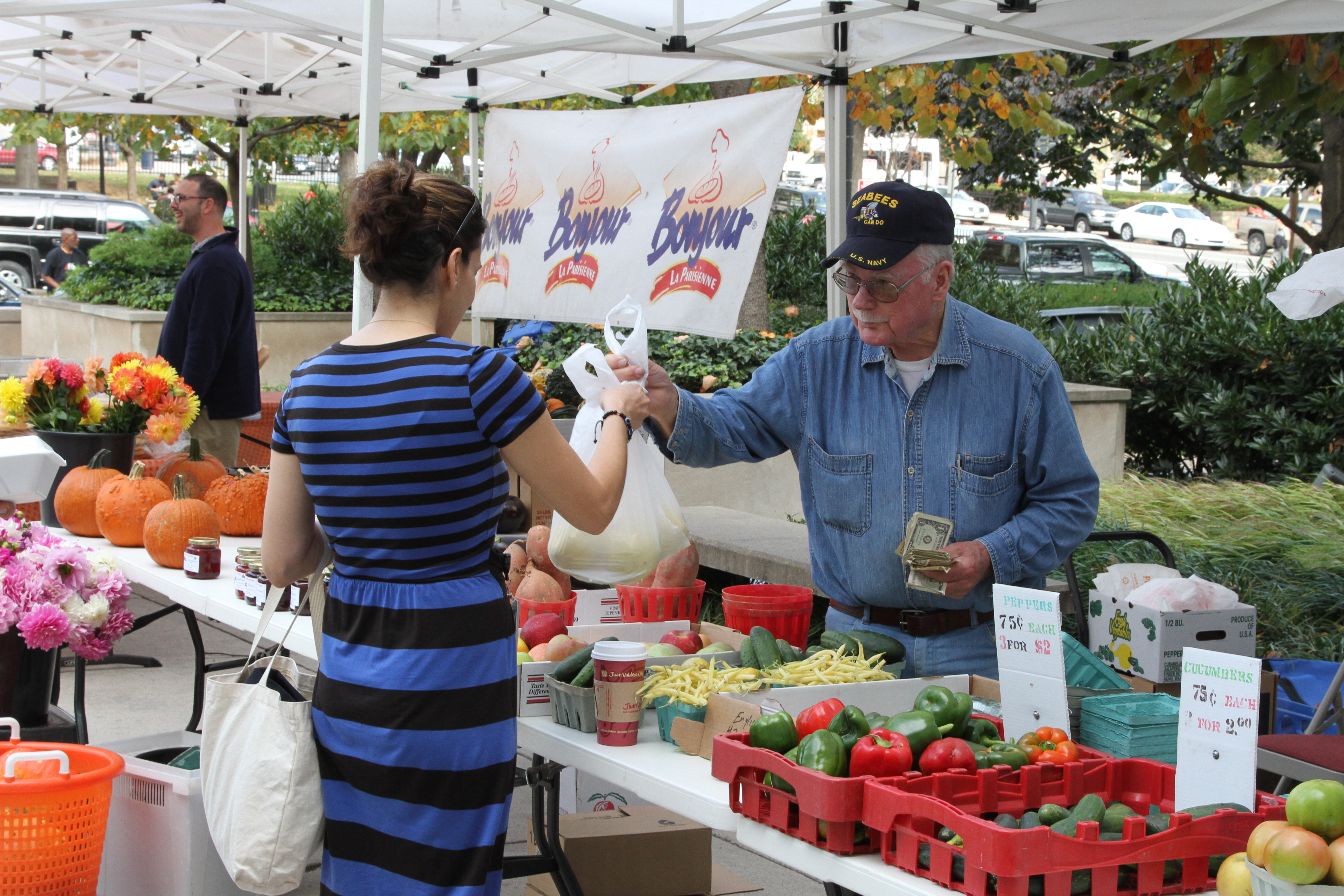 Photo of a lady buying vegetables from a veteran at a local farmers market.