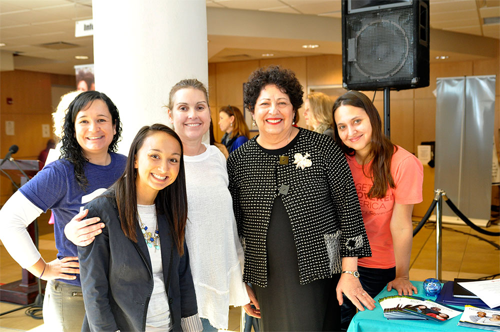 Director Archuleta stands with young women at an event in Tampa