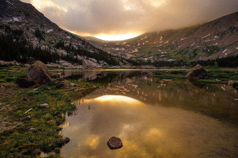 Photo of Rocky Mountain National Park. Mountains in the background with a golden sunset. Pond is in the forefront of the photo with a reflection of the mountains and sunset.