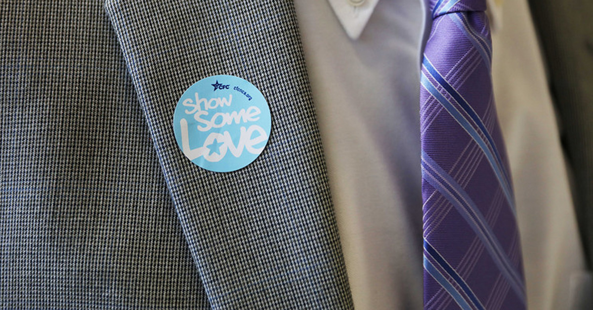 Picture of a gray suit, with a purple tie. On the suit is a blue circle sticker. It says 'Some Some Love'in white  and has the CFC logo at the top in dark blue.