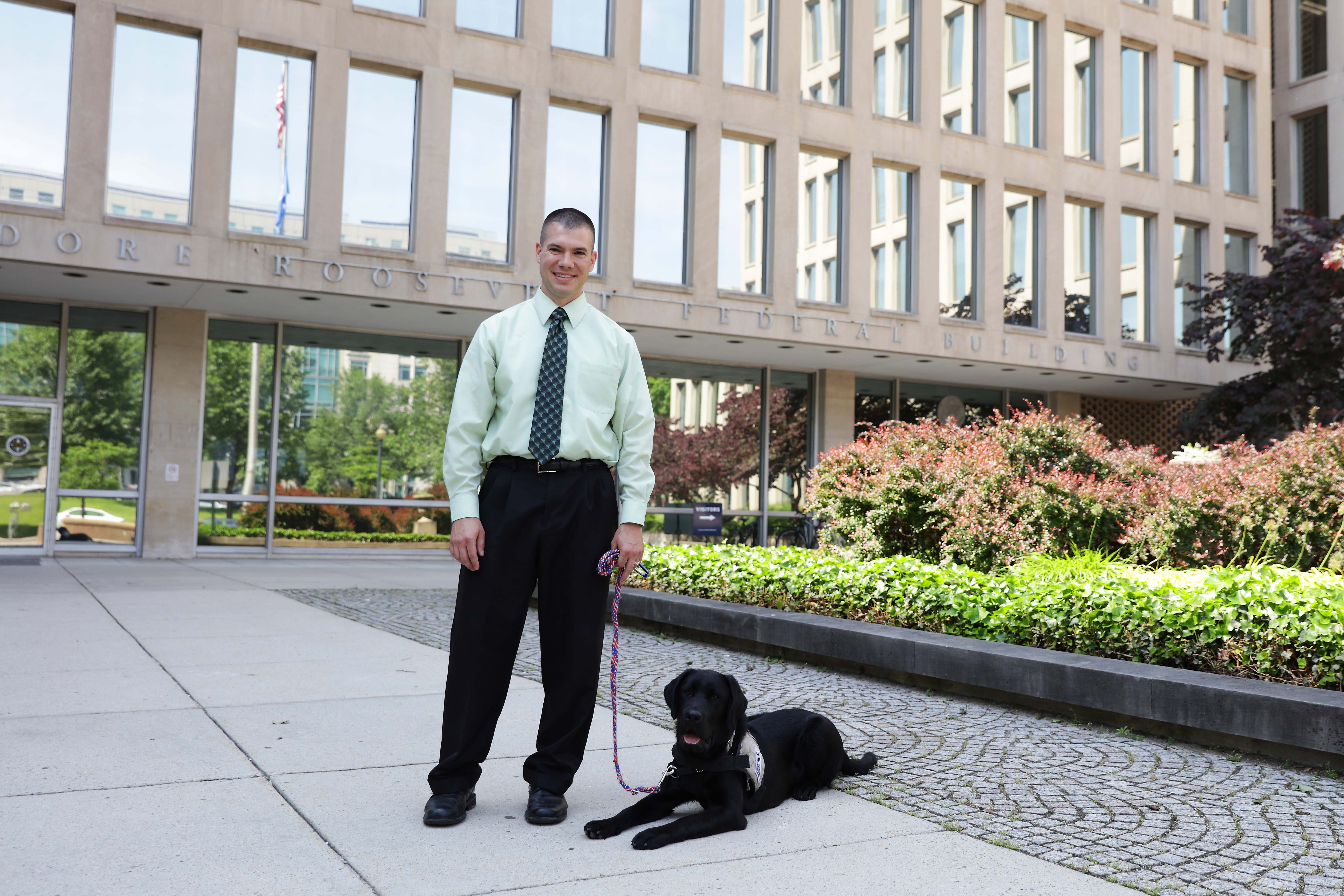 Photo of a man and his dog posing in front of OPM's building.