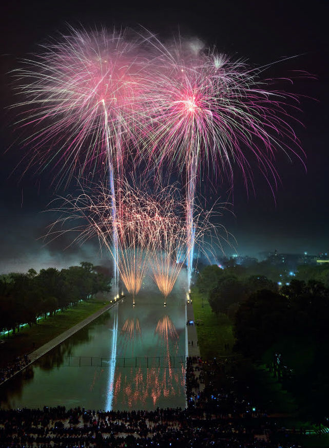Four red fireworks over the reflecting pool on the mall.