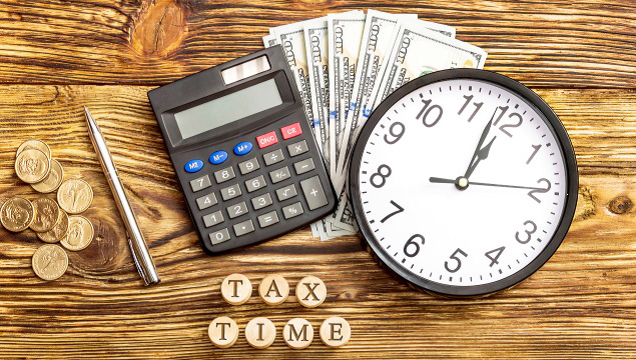 Tax Time graphic featuring currency, calculator, and clock