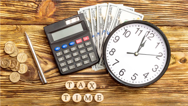 IRS Tax Time Graphic Showing Coins, Pen, Calculator, Currency, and Wall Clock