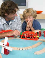 Adult playing trains with a boy