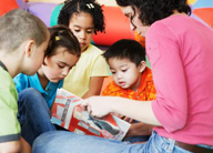 a group of children being read a book by an adult child care taker